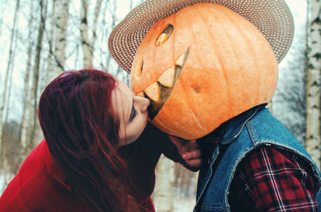 Halloween Scarecrow with a pumpkin on his head and an evil witch with a broom in her hands met in the woods Archivio Fotografico