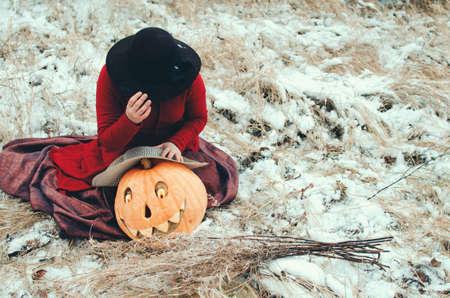 witch grieves over a mask carved from a Halloween pumpkin 写真素材