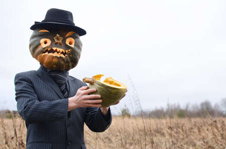 man in a fancy dress celebrates Halloween in an autumn field among dry grasses