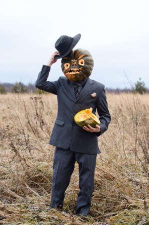 man in a fancy dress celebrates Halloween in an autumn field among dry grasses
