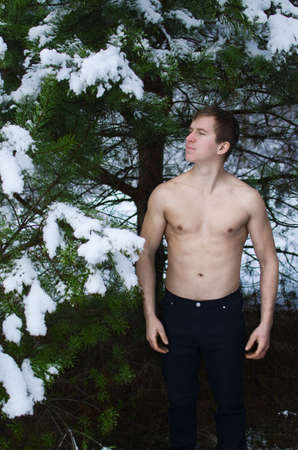 young man without a shirt in the winter forest sprinkles snow
