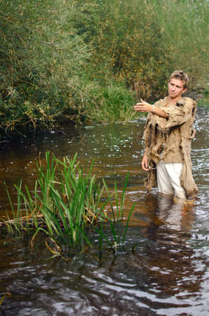 man in medieval peasant clothing stands in shallow water in the river Banque d'images