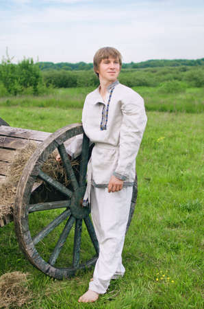 young man in national costume stands near an old cart
