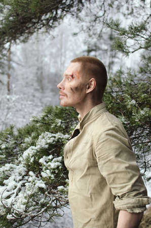 young soldier in a world war II uniform is sitting in a winter forest looking up