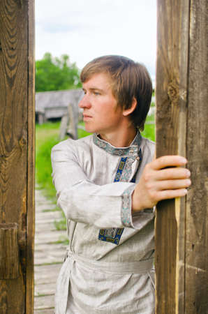 guy in old clothes opens a large wooden gate 写真素材