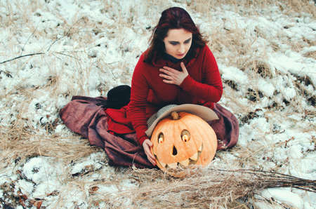 witch grieves over a Halloween carved pumpkin sitting in the snow