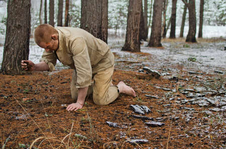 young man in a world war II uniform and barefoot kneels in a winter forest 写真素材