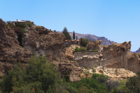 Large stone house perched on cliff in lush Arizona desert canyon.  See similar images in my portfolio.