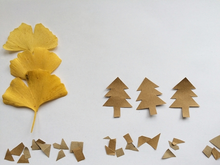 Ginkgo biloba leaf isolated and paper chrisma trees on a white background