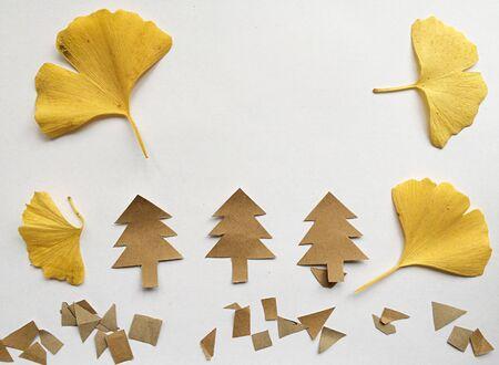 Ginkgo biloba leaf isolated and paper chrisma trees on white background