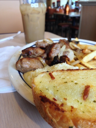 A meal consisting of french fries mashed potatoes steak tips with fried onions and garlic bread. Reklamní fotografie