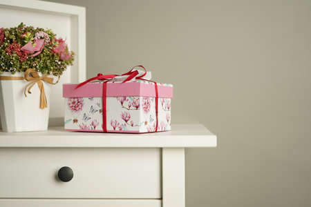a beautiful gift box lies on the bedside table next to a decorative bouquet of flowers and a white photo frame against a gray wall