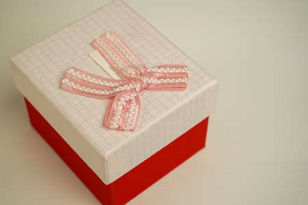 beautiful red gift box stands on a wooden bedside table