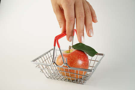 beautiful female hand with a well-groomed manicure holds a miniature size supermarket basket with a red ripe juicy whole apple on a white background