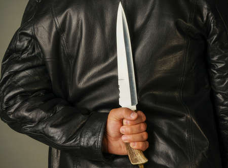 a man in a black leather jacket holds a large knife behind his back Stock Photo
