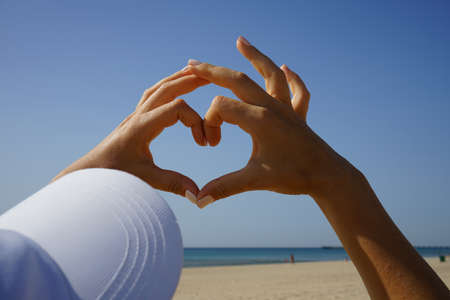 women's hands show the heart sign against the blue clear sky, sea and sandy beach