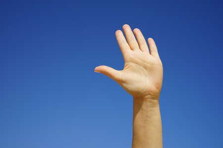 female hand close-up against a cloudless blue sky Stok Fotoğraf