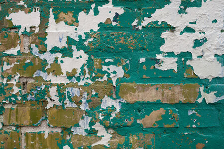 Green and White Paint Peeling off Yellow Brick Wall Stock Photo