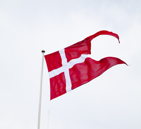 Danish Split Flag Waving on Bright Cloudy Background photo