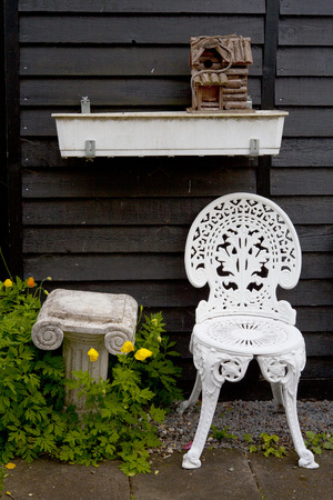 White Metal Garden Chair next to Small Column and Birdhouse photo