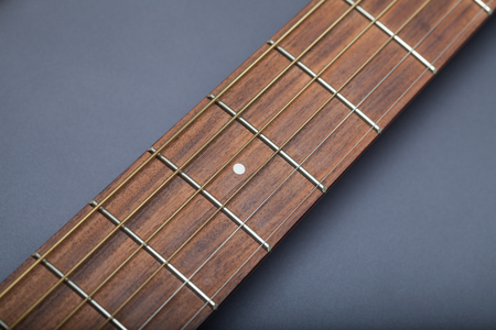 fret: Fretboard on Acoustic Guitar Close-Up on Fifth Fret