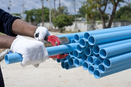 Worker cut pvc pipe in construction site Stock Photo - 13055244