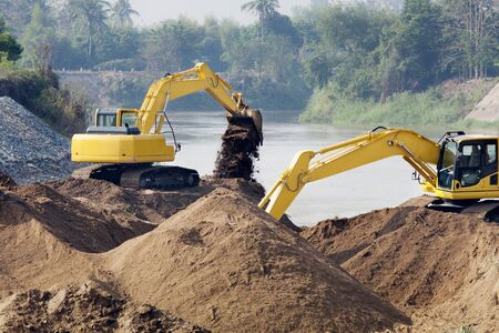excavator machine moving earth at river for protect flood photo