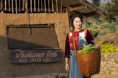 earthen: Maehongson, THAILANDIA - FEB 12: Earthen Casa di Villaggio, Lisu Hill trib� ragazza in costume tradizionale, con la sua verdura dal giardino al mattino il Feb 12, 2011 in Maehongson, Thailandia.