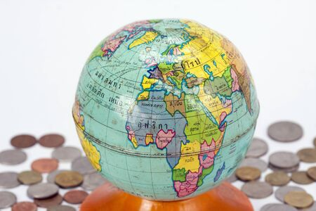 Vintage globe on the pile of coins Stock Photo - 14525061