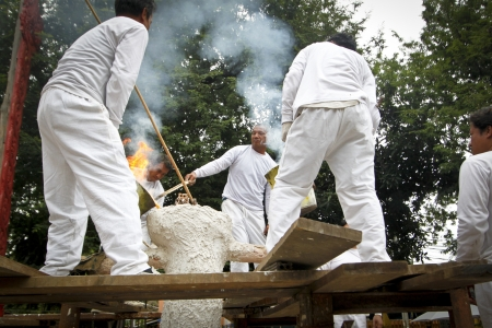 molee: CHIANG MAI  THAILAND - AUGUST 12 : Buddhist metal cast ceremony for buddha statue , Pouring molten metal in mold  . Aug 12,2012 in Lok Molee Temple, Chiangmai, Thailand.