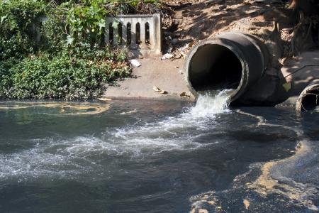 desague: Dirty drenaje, contaminación del agua en el río Foto de archivo