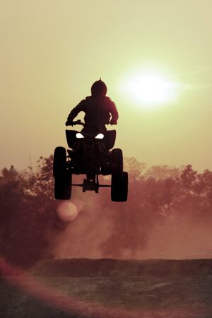 Silhouette ATV jump on dirt track photo
