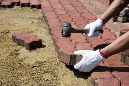 a worker laying red concrete paving blocks