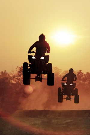 Silhouette ATV jump on dirt tract  photo