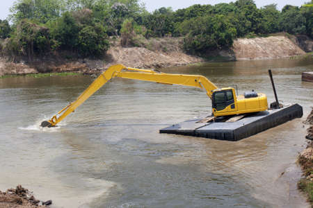 sand quarry: excavator machine works at river for protect flood