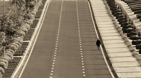 lonely road: A man walking alone along the road  Stock Photo
