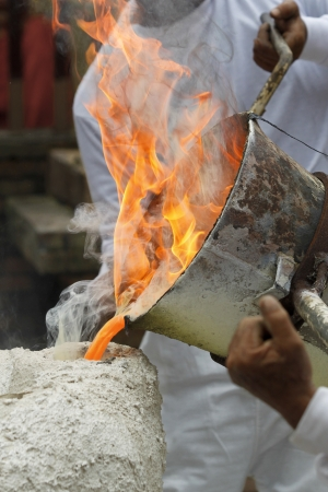 metal casting: pouring liquid metal into mold