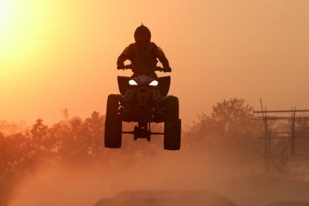 atv: Quad bike Jump in the sunset  Stock Photo