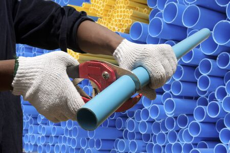 pvc: Worker cut pvc pipe in construction site Stock Photo