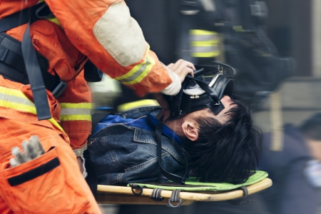 The rescue workers move hurt person with a stretcher urgently.