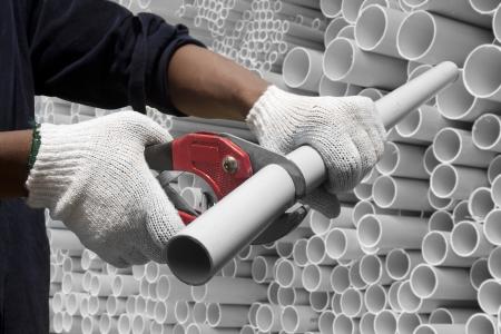 tuberias de agua: Trabajador cortar tubos de pvc en el sitio de construcci�n Foto de archivo