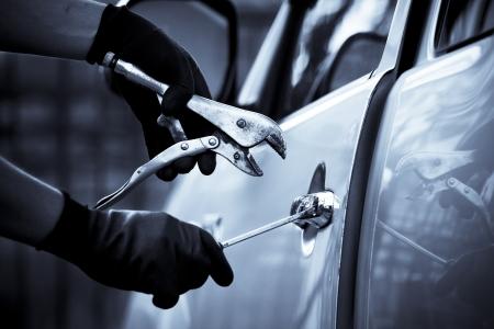 car theft: Ladr�n de coche con una herramienta para entrar en un coche Foto de archivo
