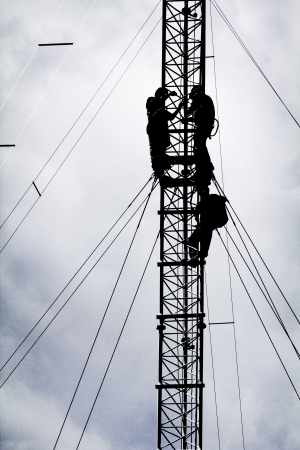 silhouette of three workers repairing communication tower