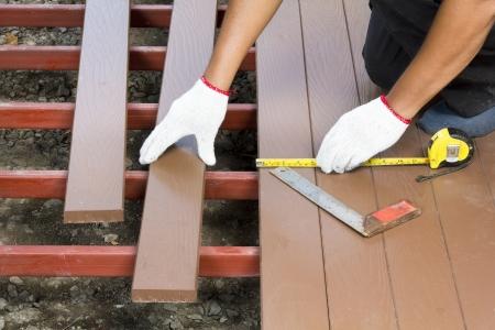 Worker installing wood floor for patio  photo