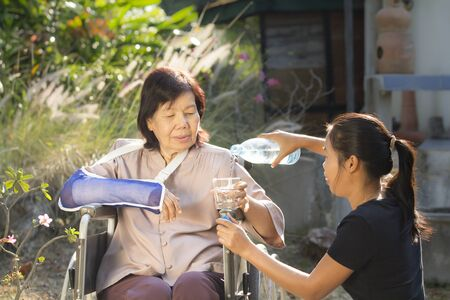 personas discapacitadas: Joven asiático es cuidar la mujer mayor, Tailandia