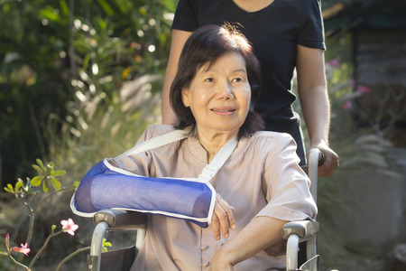 cast: Asian senior woman with broken wrist on wheel chair Stock Photo