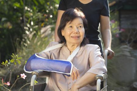 broken wrist: Mujer mayor asi�tica con fractura de mu�eca en silla de ruedas Foto de archivo