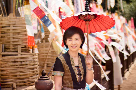 Woman with religion flag at temple in Songkran festival photo