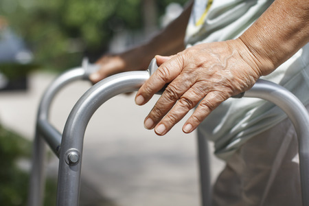 Senior woman using a walker cross street  Stock Photo