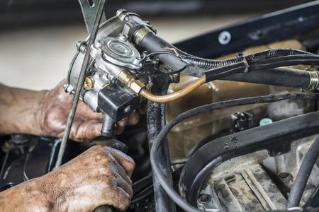 Mechanic install new gas vaporizer in old car , bi-fuel alternative photo